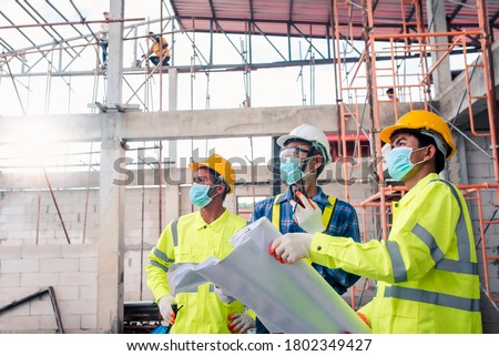 A team of construction engineers and three architects put together a Coronavirus or Covid-19 protective mask during construction design at the construction site. #1802349427