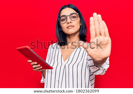 Young beautiful latin woman holding touchpad with open hand doing stop sign with serious and confident expression, defense gesture