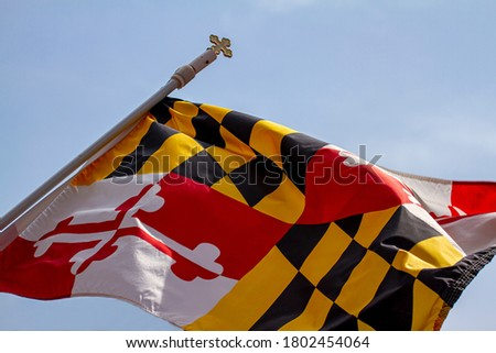 Isolated close up photo of Maryland State Flag against clear sky.  Flag is attached to a pole with a cross on top. The unique design is a combination of Calvert's banner and Crossland banner sections.
