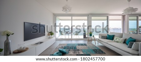 Modern living room with designer furniture. Sofa with light cushions and balcony view. Nobody inside. Frontal view, panorama Royalty-Free Stock Photo #1802457700