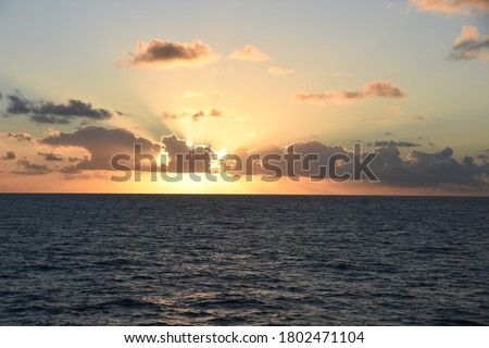 Sunset in Atlantic ocean during calm weather with the sun behind the heap clouds. Sunrays have orange colour.  Picture was taken from the navigational bridge of the cargo container vessel.