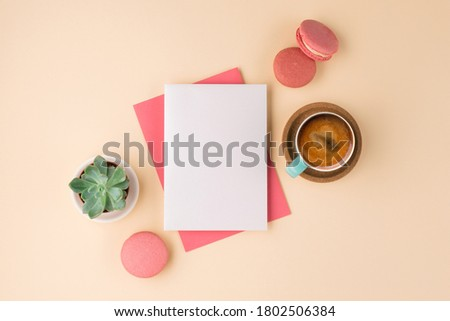 Mockup with postcard, sweets and cup of coffee on beige background. Pink envelope with empty card and green plant. Flat lay, top view. Royalty-Free Stock Photo #1802506384