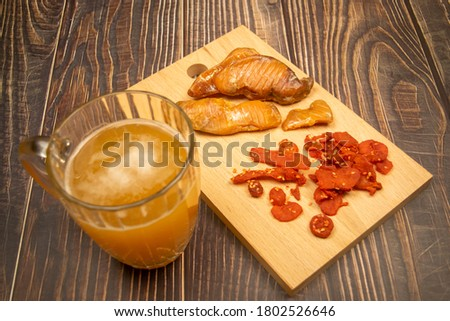 Dried halibut caviar and dried crab meat on a wooden serving Board and a mug of beer on a wooden table. Close up.