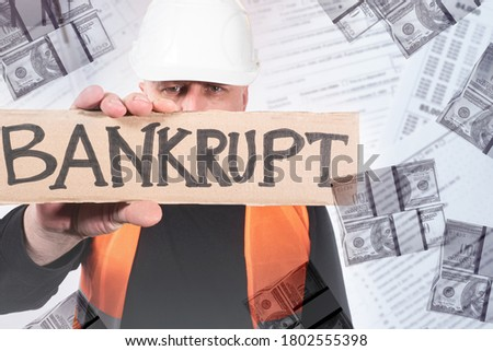 Builder declares himself bankrupt. Inscription bankrupt on a cardboard poster. Concept - builder cannot pay the bills. Businessman builder went bankrupt. Money and financial documents next to a man Royalty-Free Stock Photo #1802555398