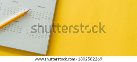 close up top view on white calendar with pencil and month schedule to make appointment meeting or manage timetable each day lay on yellow color panoramic background for planning work and life concept