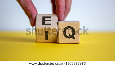 Hand flips a cube and changes the expression 'IQ' to 'EQ'. Beautiful yellow table, white background. Concept of emotional and  intelligence quotient. Copy space. Royalty-Free Stock Photo #1802593693