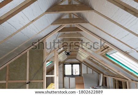 Loft conversion, unfinished project, silver insulation, roof windows, wood structure of the walls, selective focus Royalty-Free Stock Photo #1802622889