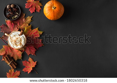 Autumn composition - Pumpkin Spice Latte, autumn maple leaves and pumpkins  on black background, creative flat lay, top view, copy space. Seasonal autumn concept with coffee drink. Royalty-Free Stock Photo #1802650318