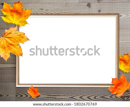 Gold photo frame on wooden background with autumn leaves, mock up