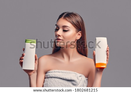 Portrait of attractive young woman with two shampoos on grey background. Making choice. Women care Royalty-Free Stock Photo #1802681215