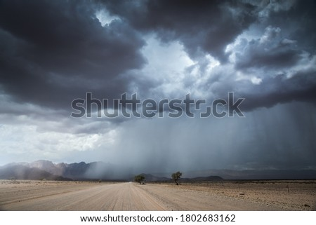 A horizontal landscape photograph of a road leading to a massive dramatic rain and thunder storm with mountains in the distance in the dry Namib Desert near Sesriem and Sossusvlei. Royalty-Free Stock Photo #1802683162