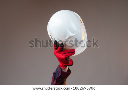 White construction helmet close-up. The man makes a greeting gesture with a white construction helmet. A gloved hand raises the helmet above his head. #1802695906