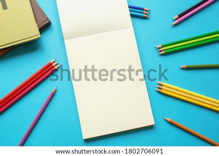 School concept. Colorful colored pencils, books and open sketchbook on blue paper background. Flat lay, free space for text or picture
