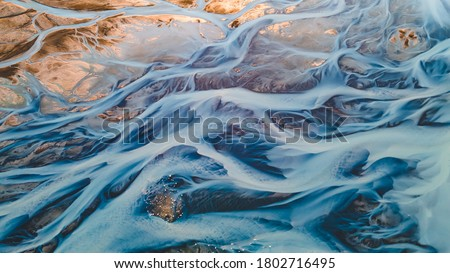 A glacial rivers from above. Aerial photograph of the river streams from Icelandic glaciers. Beautiful art of the Mother nature created in Iceland. Wallpaper background high quality photo Royalty-Free Stock Photo #1802716495