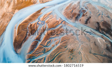 A glacial rivers from above. Aerial photograph of the river streams from Icelandic glaciers. Beautiful art of the Mother nature created in Iceland. Wallpaper background high quality photo Royalty-Free Stock Photo #1802716519