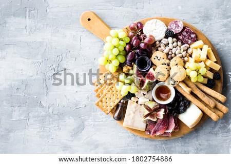 Charcuterie board. Cheese platter: Parmesan, maasdam, camembert, cheddar, gouda with prosciutto, salami, fruits and nuts. Assortment of tasty appetizers or antipasti. Top view. Copy space. #1802754886