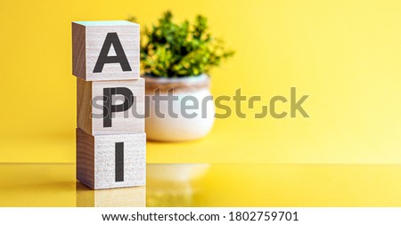 Word API is made of wooden building blocks on a light yellow background. API - Application Programming Interface.