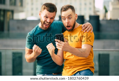 Two happy excited fan friends in euphoria mood after winning in a bet with a smartphone in hand on stadion background Royalty-Free Stock Photo #1802760439