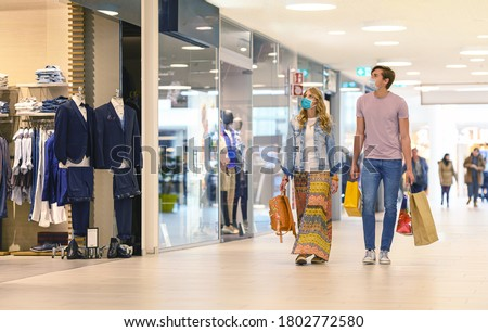Shopping at the time of Corona Virus. Handsome young and fashion couple at the shop center walking with protective surgical face mask, shopping bags in hand and looking at shop windows. Alert Covid-19 #1802772580