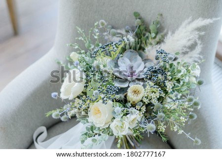 Bridal bouquet. The bride's bouquet. Beautiful bouquet of white, blue flowers and greenery, decorated with long silk ribbon lies on a gray textural background Royalty-Free Stock Photo #1802777167