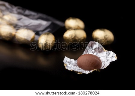 Cellophane bag of gold coloured chocolate mini easter eggs, lying down on a black surface with a couple of the eggs out of the bag. Focus is on the front egg that has been unwrapped. #180278024