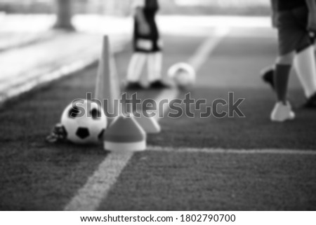Blurry picture of black and white sport background. Soccer ball with kid soccer player and soccer training equipment on green artificial turf and mini goal in soccer academy.