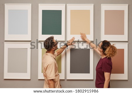 Young couple pointing at picture hanging on the wall while they visiting art gallery