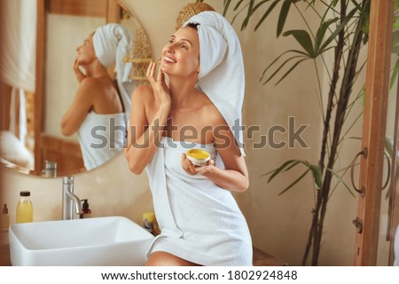 Woman After Bath. Portrait Of Happy Model Wearing Towel After Shower. Young Female Applying Anti-Aging Cream Or Mask On Facial Skin. Natural Beauty Product For SPA Treatment At Home.  Royalty-Free Stock Photo #1802924848