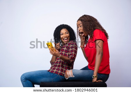 beautiful young black lady showing her friend something exciting on her phone Royalty-Free Stock Photo #1802946001