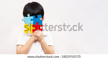 Autism awareness day April 2 - Studio Portrait of a little cute asian child cover his face with the colorful puzzles pieces. Autism Spectrum Disorder concept, ASD, Syndrome, Symptoms, Copy space