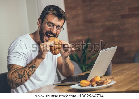 During the morning, the man sits at a table in the dining room and has breakfast