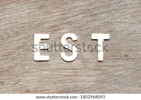 Alphabet letter in word  est (abbreviation of established, estimated, eastern time zone, expressed sequence tag) on wood background Royalty-Free Stock Photo #1802968093