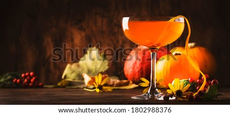 Satan whiskers, orange halloween cocktail with gin, vermouth, juice and liquor, vintage table setting with festive aurumn decor #1802988376