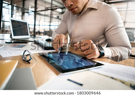 Cropped view of confident businessman in formalwear pointing at tablet computer, analyzing stat and dynamic on forex charts, working in office Royalty-Free Stock Photo #1803009646