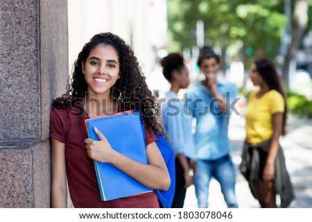 Laughing brazilian female student with group of young adults outdoor in city in summer Royalty-Free Stock Photo #1803078046