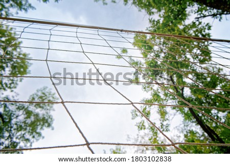 The volleyball net is on the background of the sky with clouds. The net is stretched between the trees in the yard. Concept for street sports, outdoor games and competitions. #1803102838