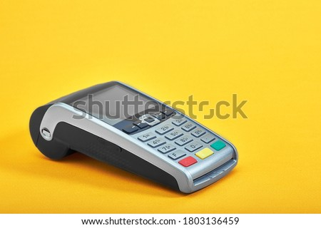 Payment terminal, compact POS terminal on yellow background top view copy space. Royalty-Free Stock Photo #1803136459