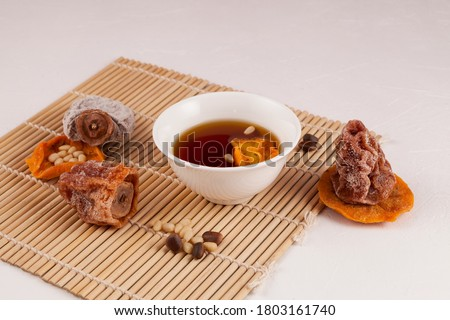 Korean iced fruit tea or chilled punch. It is made from dried persimmons (gotgam) and cinnamon, sometimes ginger and pine nuts are added. Close-up, selective focus. Royalty-Free Stock Photo #1803161740