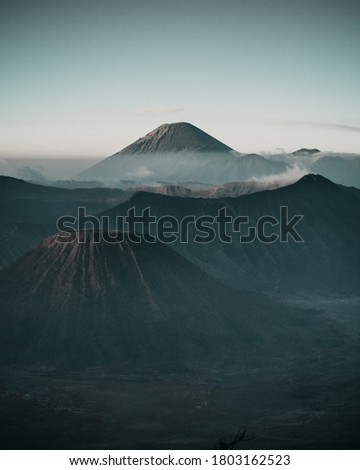 A close dramatic warm scenery at the dawn in Mount Bromo with a cloudy sky above the mountain. It is one of the most popular active volcanoes in Indonesia. #1803162523