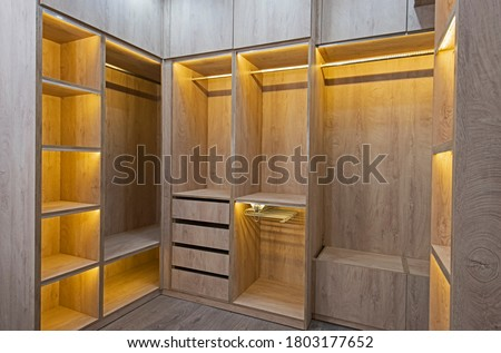 Interior design decor furnishing of luxury show home bedroom showing walk in wooden wardrobe closet furniture Royalty-Free Stock Photo #1803177652