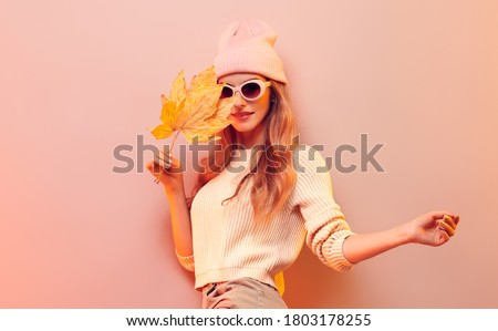 Fashionable hipster woman in Trendy autumn fall outfit, stylish hair, makeup. Blonde model in jumper, fashion jeans having fun smiling. Beautiful girl in autumnal beanie hat with maple leaf #1803178255