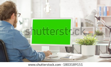 Shot of a Young Bearded Male Using His Personal Desktop Computer with Green Screen Mock-up Template. He Works in a Bright Modern Office.