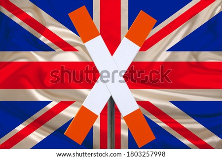 customs sign, stop, attention on the background of the silk national flag of Great Britain, the concept of border and customs control, violation of the state border, tourism restrictions