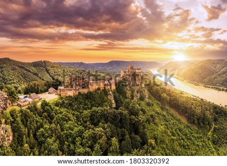 Beautiful landscape with Aggstein castle ruin and Danube river at sunset in Wachau walley Austria. Amazing historical ruins. Original german name is Burgruine aggstein. Little castle in english. #1803320392