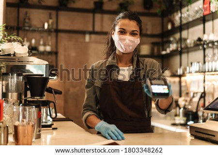 Woman barista wearing medical face mask holding cashless terminal to pay for order at the counter Royalty-Free Stock Photo #1803348262