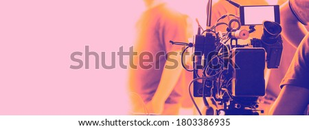 Behind the scenes of video recording or filming online movie by 8K high definition digital camera and professional monitor. And flare lighting set up with film crew team in the studio production.