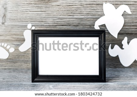 Background for Halloween. Black frame with free space on the table with a wooden background. White ghostly shapes and white footprints in the background are blurred. Halloween concept and ideas.