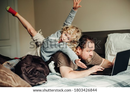 Work from home with kids children. Father working on laptop in bedroom with child daughter on his back. Funny candid family moment. New normal during coronavirus self-isolation quarantine. Royalty-Free Stock Photo #1803426844