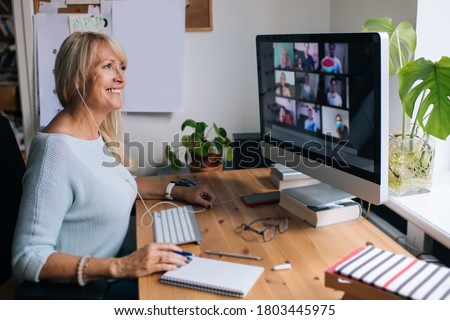 Smiling mature woman having video call via computer in the home office. Online team meeting video conference calling from home. Attractive Businesswoman Telework. Business video conferencing.  #1803445975