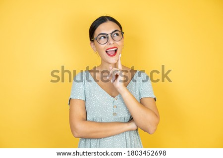 Young beautiful woman wearing glasses standing over isolated yellow background looking side confident, thinking with crossed arms and hand raised on chin